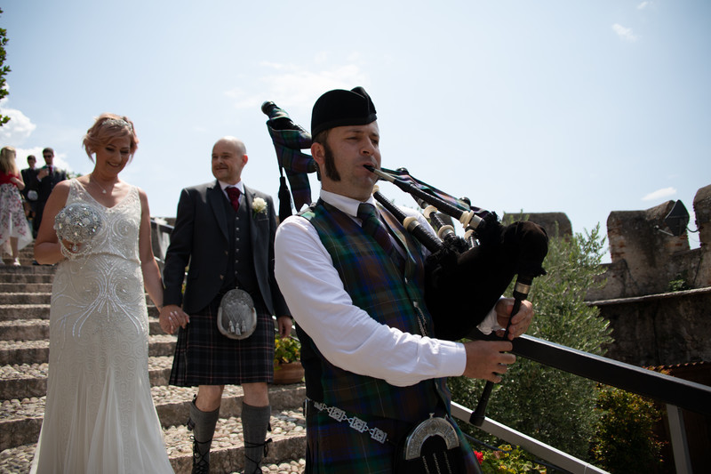 Happy married couple and piper in Malcesine castle