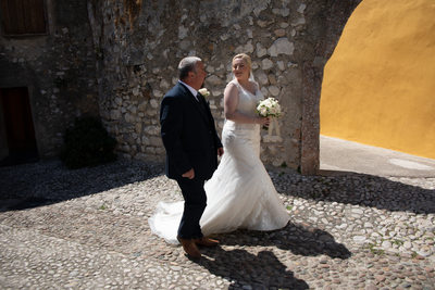 Bride and her father walking towards Malcesine Castle