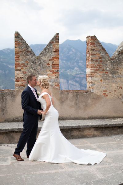 Claire and Adam kissing in Malcesine Castle, Lake Garda