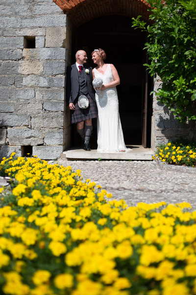 happy bridal couple with flowers in Malcesine castle