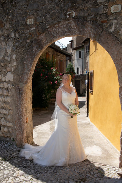 Beautiful bride staring at Malcesine Castle