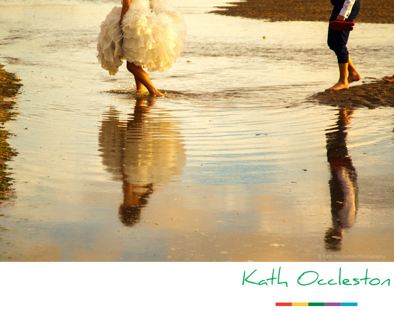 Reflections of bride & groom in the sea