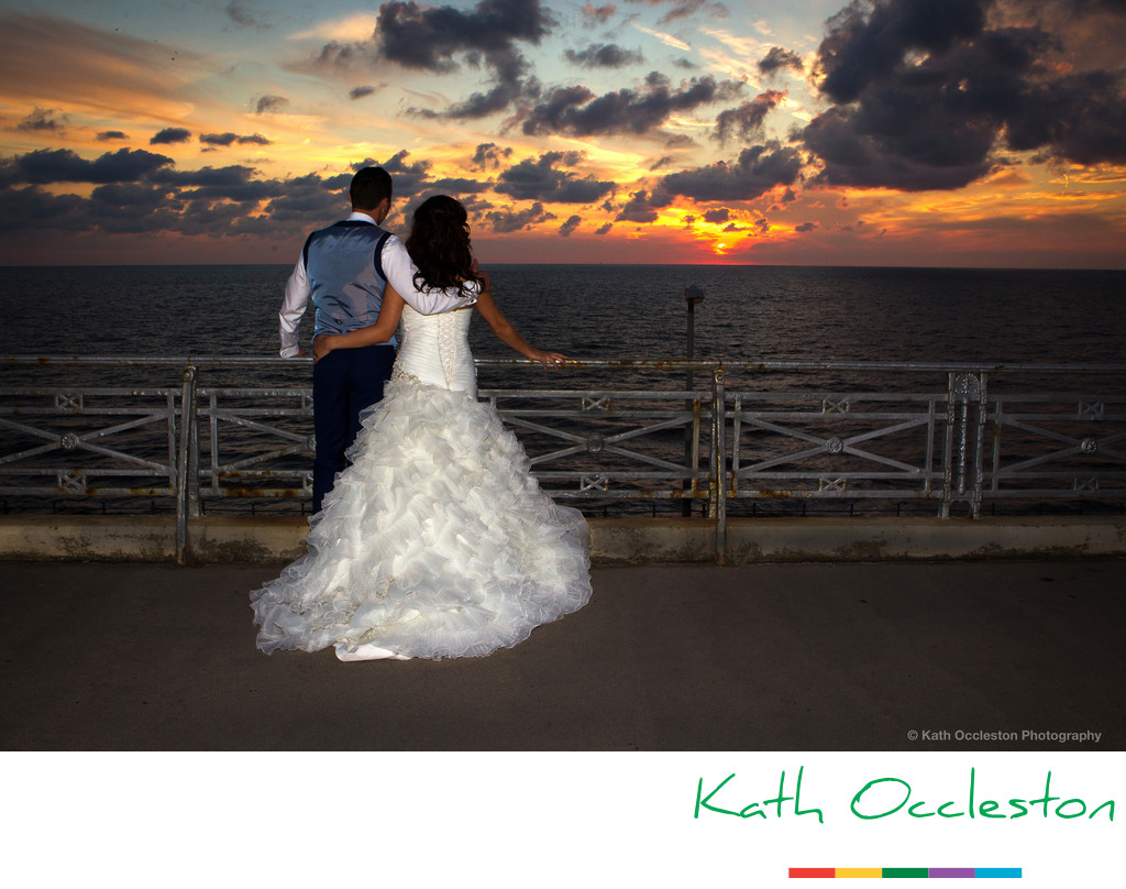Bride & Groom watching the sun set over the sea