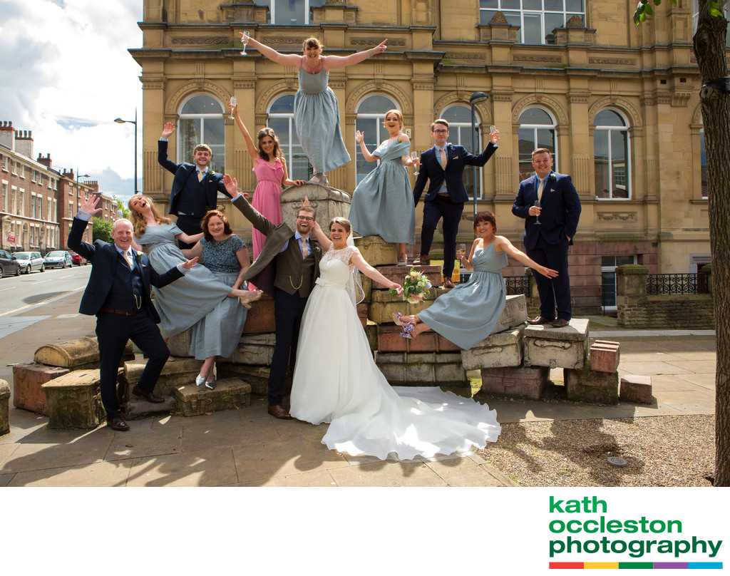 Fun wedding group photo on the Liverpool Suitcases