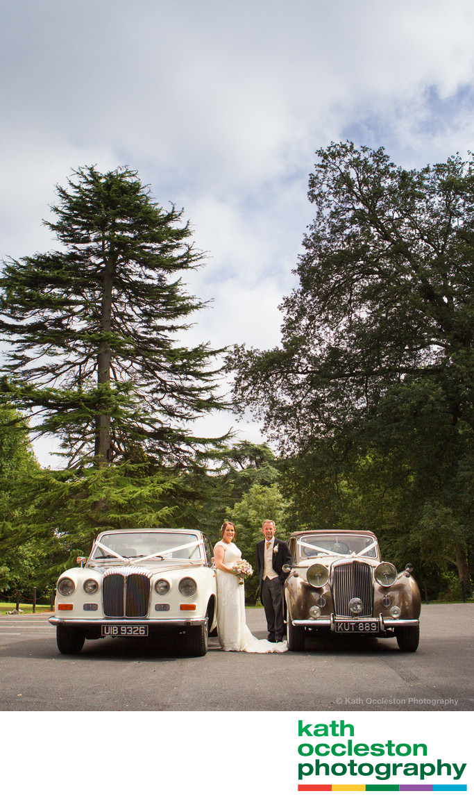 Couple with wedding cars at Bartle Hall