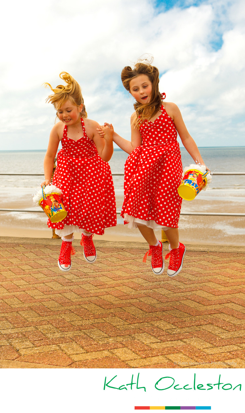 Flower girls jumping in red polka dot dresses