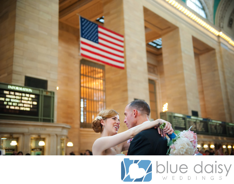 The wedding couple embrace under American flag
