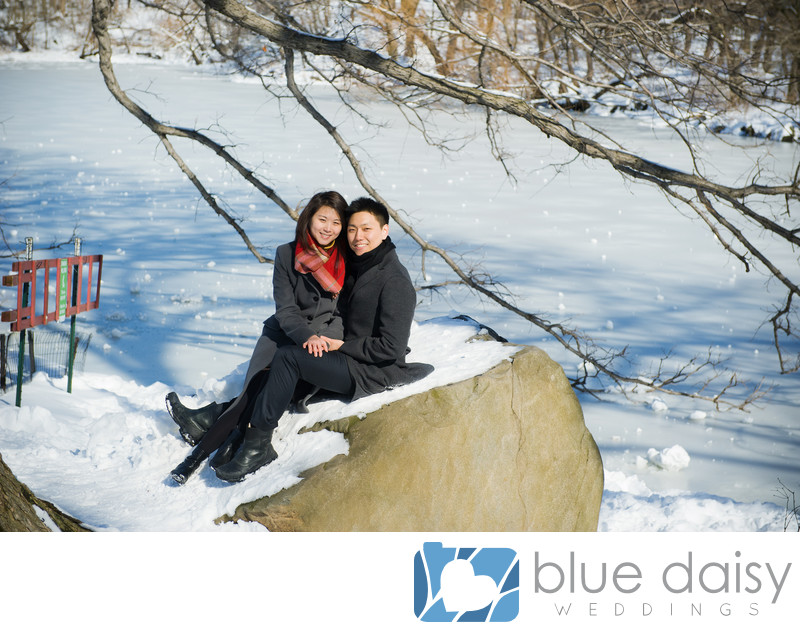 Engaged couple sitting on snow covered rock by the Lake