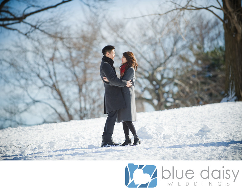 Engaged couple embrace in snowy Central Park NYC