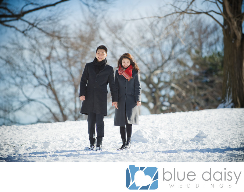 Engaged couple taking a stroll in the snowy park
