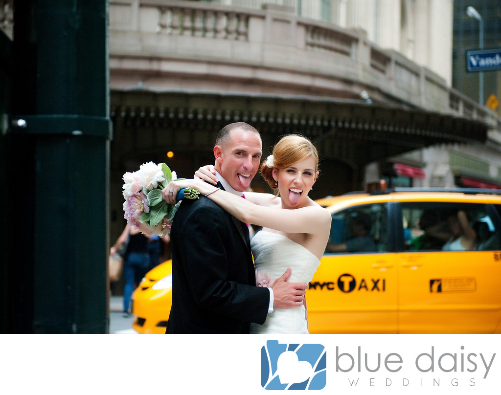 Bride and groom sticking tongue out with yellow cab