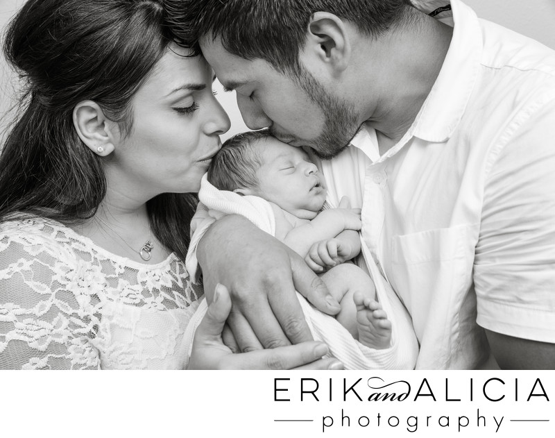black and white family portrait kissing newborn girl