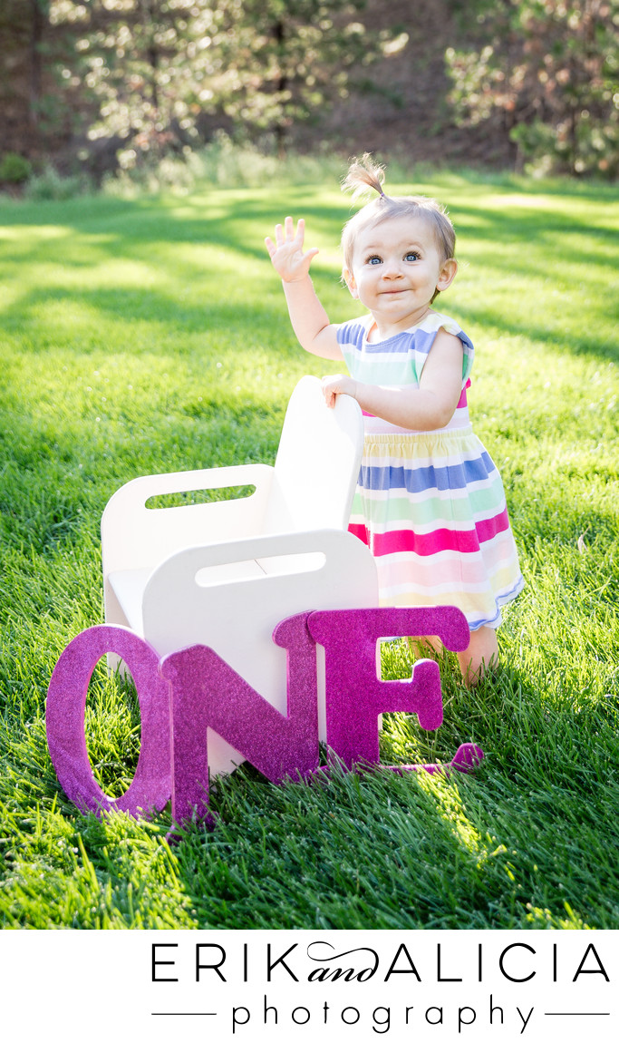 pink one year old waving hello