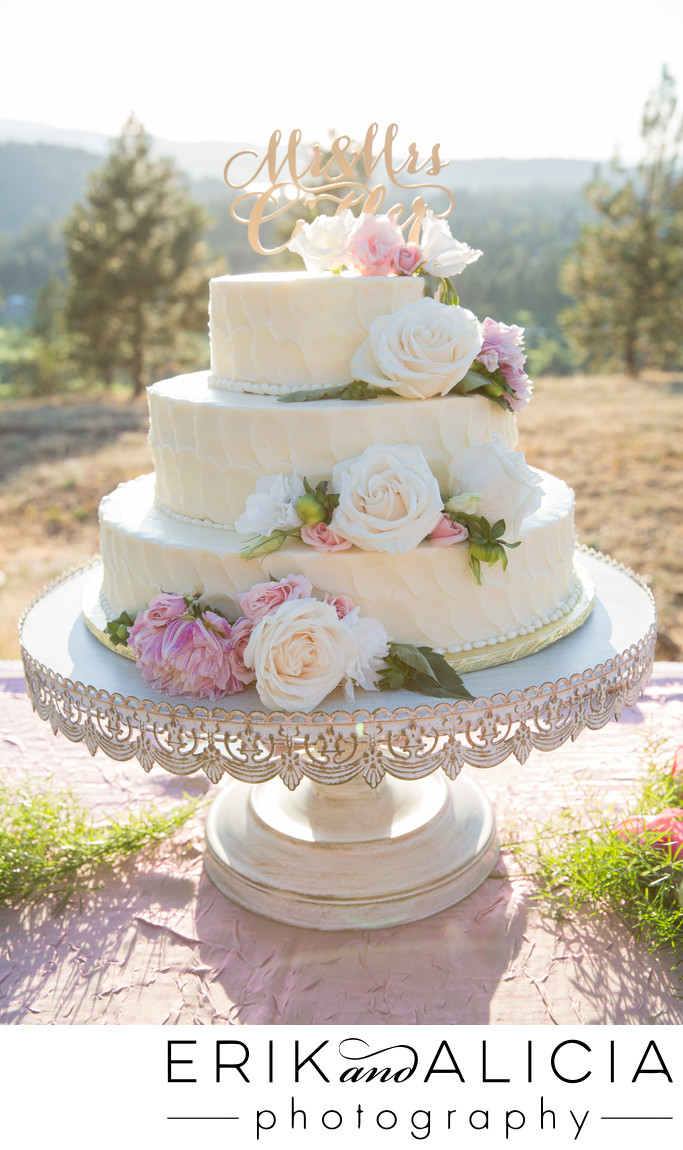 three tier wedding cake with white and pink flowers