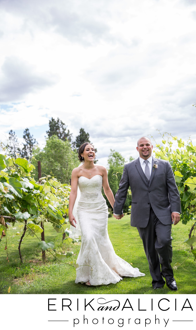 Laughing bride holding grooms hand walking in vineyard