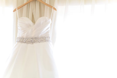 strapless wedding dress on hanger in window light