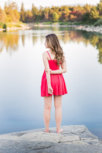 side profile of girl standing at a glassy river