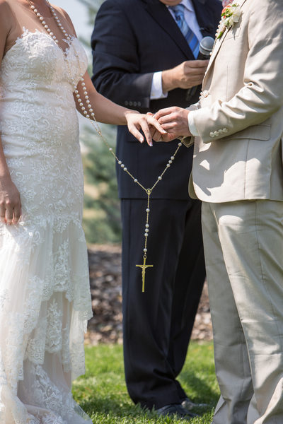 Couple wears double rosary while groom places on ring