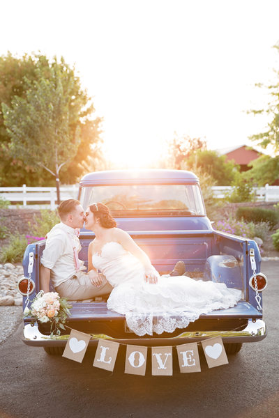 Sunset kiss in old blue pickup truck bed