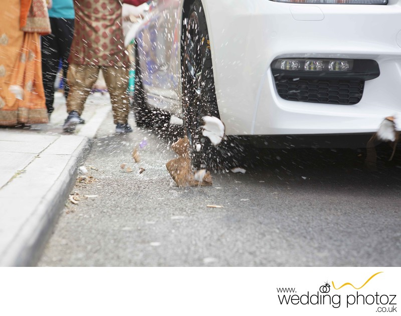 Indian wedding driving over a coconut