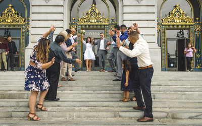 Fun newlywed couple leaving the San Francisco City Hall after their Wedding