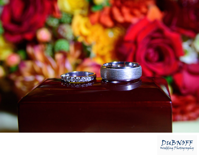 Wedding Rings on a box with Bouquet behind