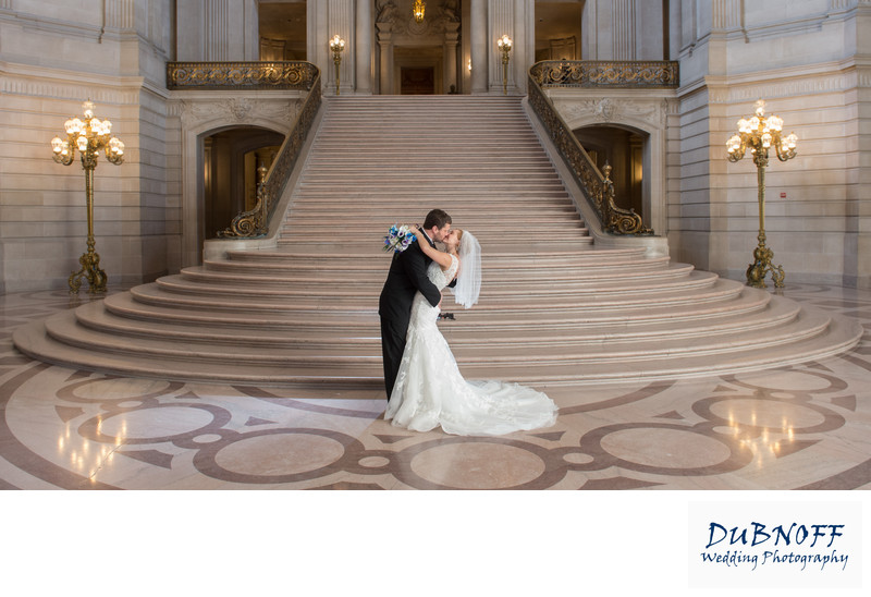 Bride and Groom Kissing in front of the Grand Staircase with beautiful wedding dress