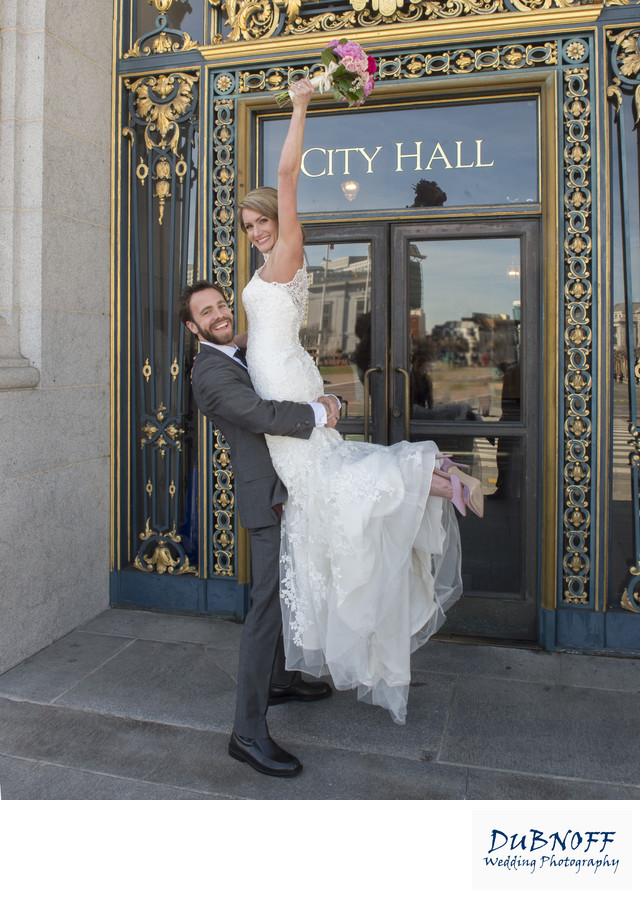 Bride Cheering in front of City Hall Sign with Bouquet