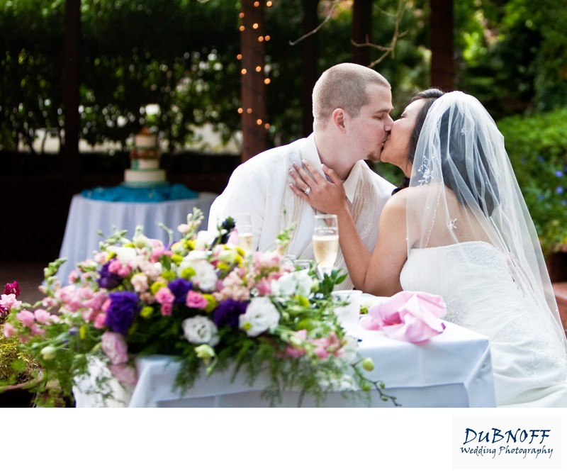 Newlyweds Kissing at the head table at Wildwood Acres