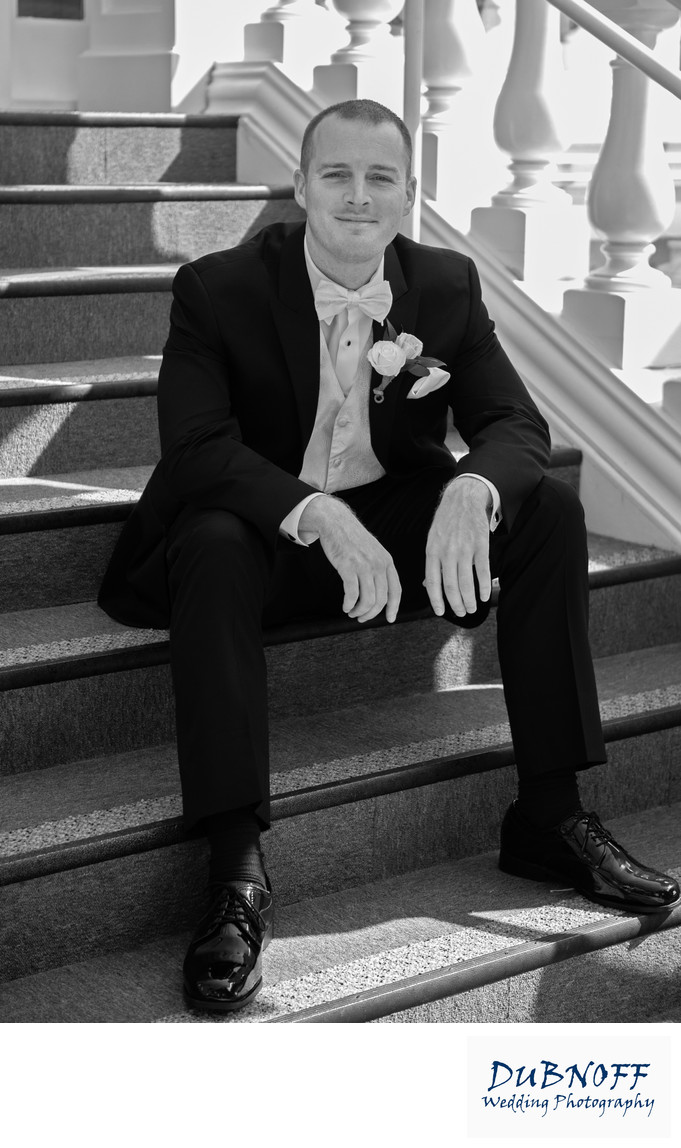 groom on mansion stairs black and white photography