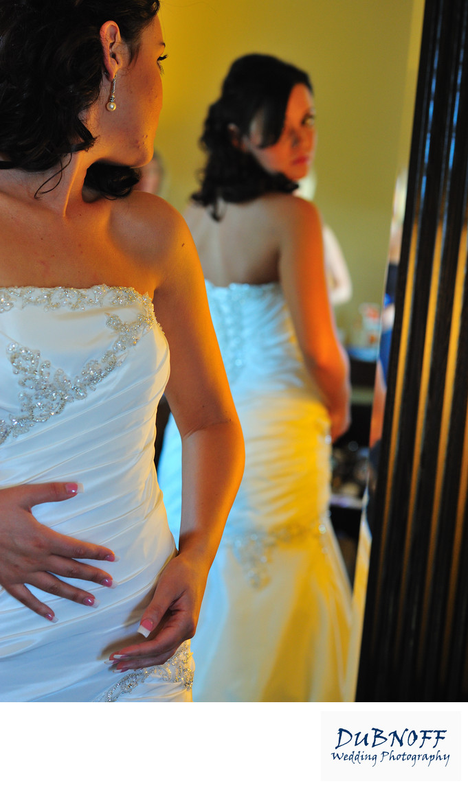 bride looking at back of dress
