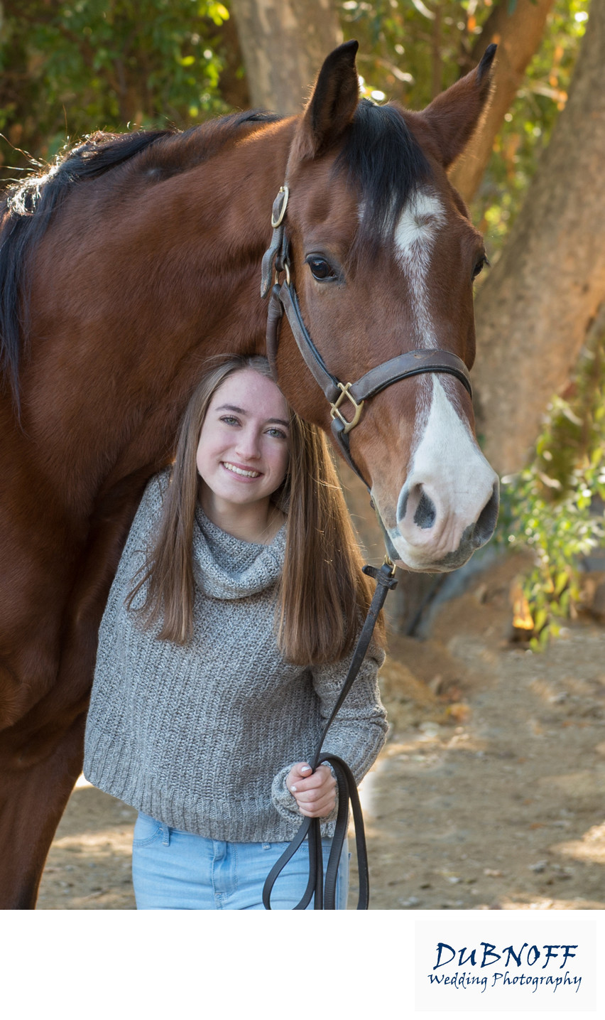 Girl Posing Under Horse during High School Senior Portrait Session