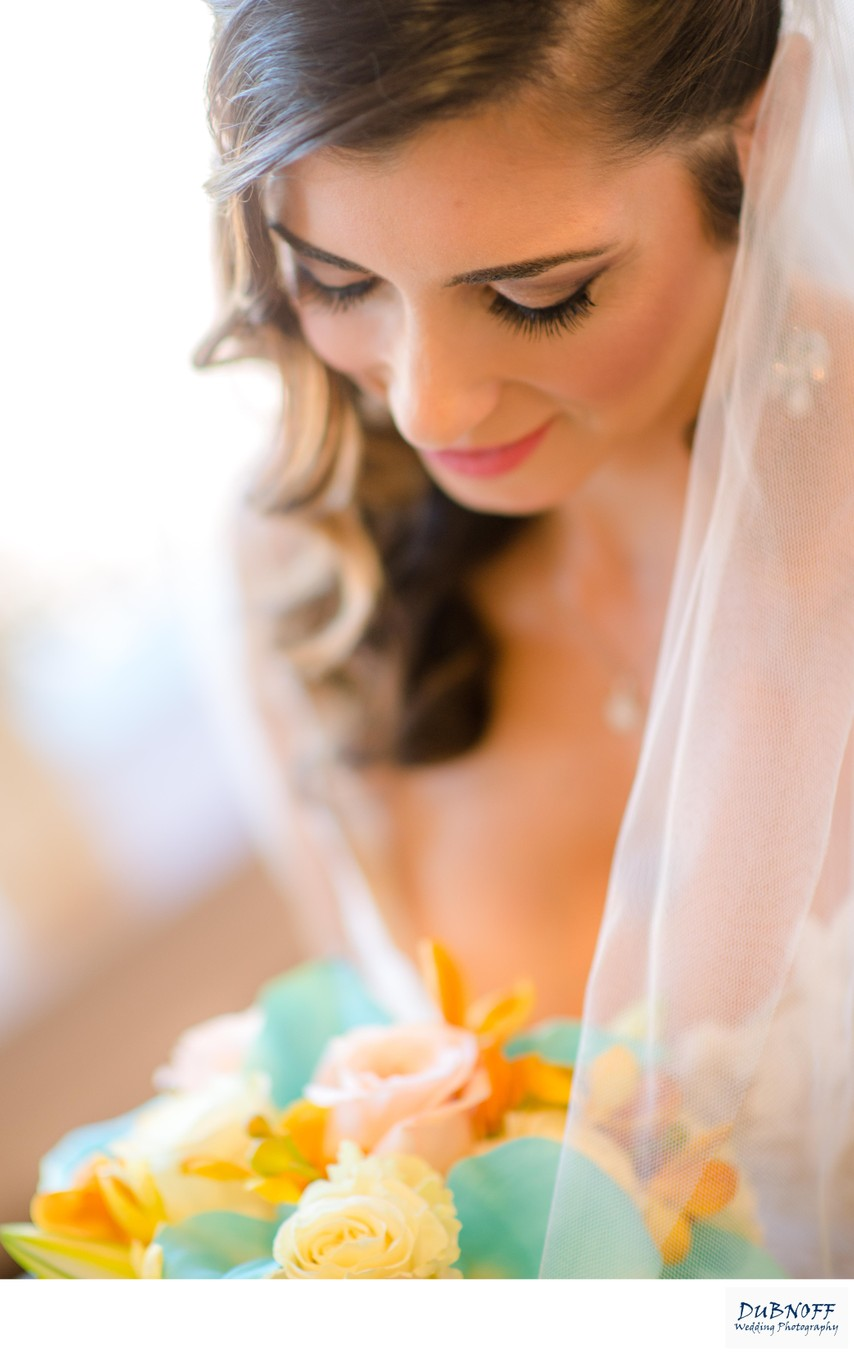 Head Shot of Beautiful Bride Looking down at her flowers