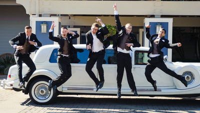guys wedding jump in front of a limo by the Berkeley Marina