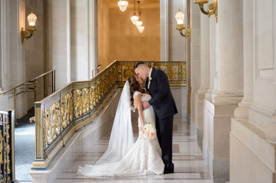 Groom Kissing Bride with glowing veil at SF City Hall