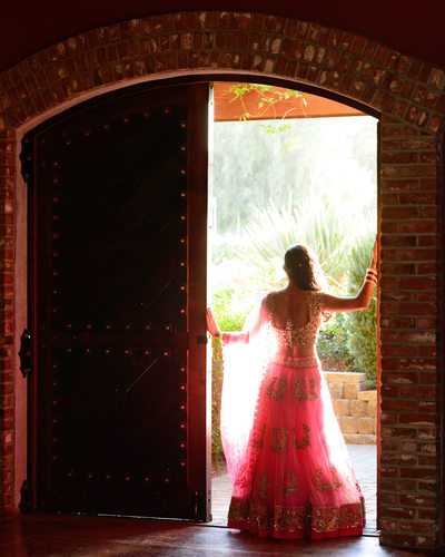 Bride in the Sunlit doorway into the wine cellar in the Bay Area