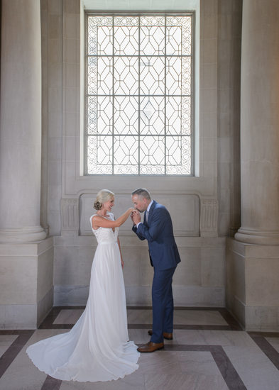 San Francisco City Hall Nuptials with Groom kissing Brides hand
