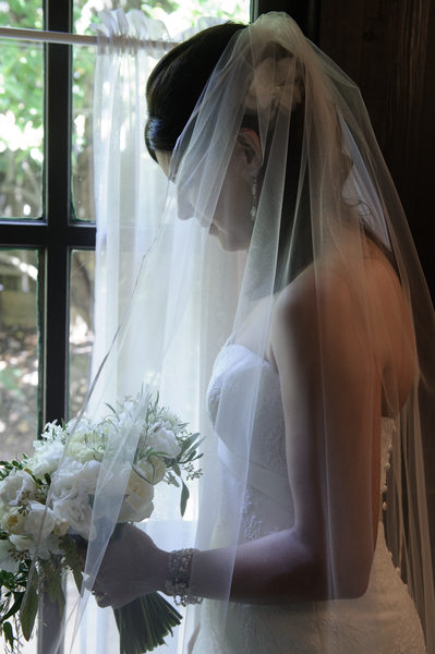 bride profile looking out the window with bouquet