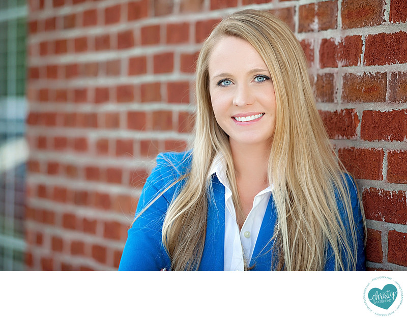 Realtor headshot outside with brick wall
