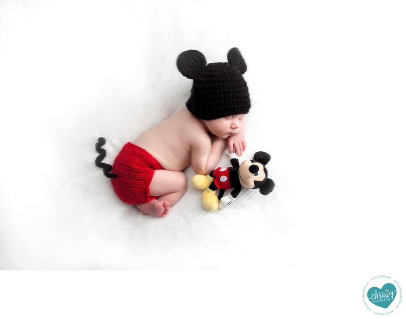 Mickey Mouse newborn holding Mickey'shand
