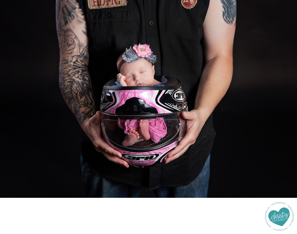 Newborn in momma's motorcycle helmet