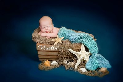 newborn baby in a mermaid tail on a tiny boat
