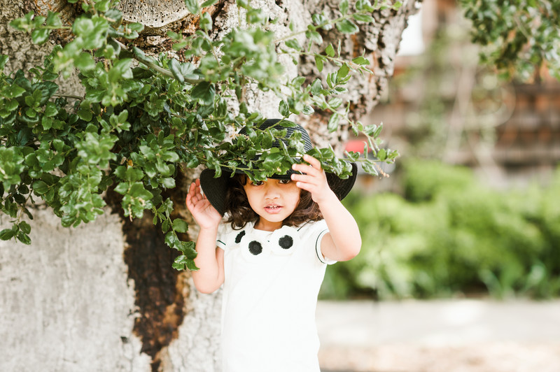 Little girl with hat by tree in family photo session