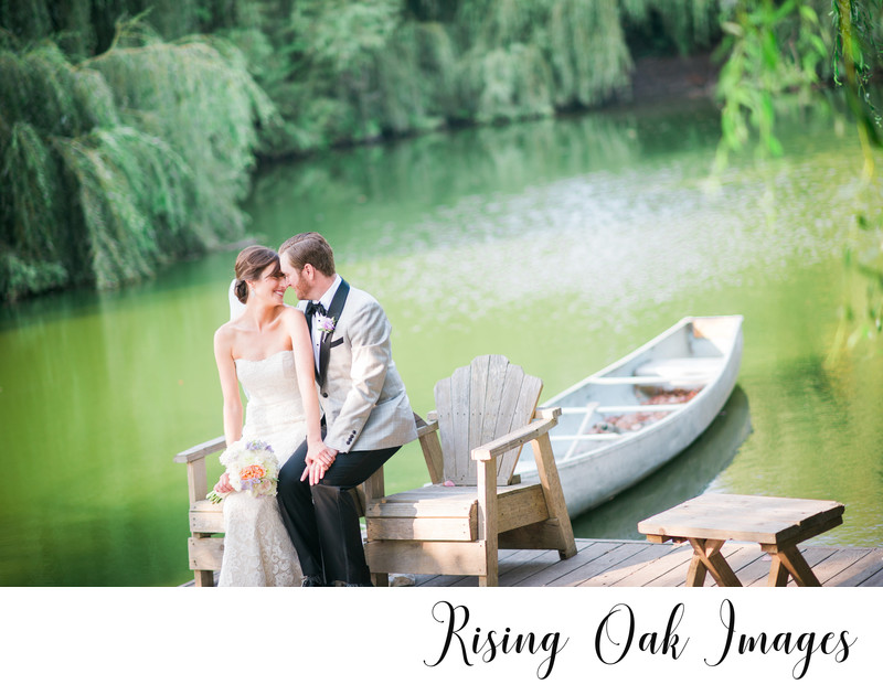 Bride and Groom sit on dock by beautiful lake in hill country