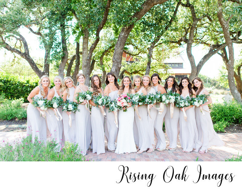 Bridesmaids under oak trees at Ian's Chapel in Camp Lucy