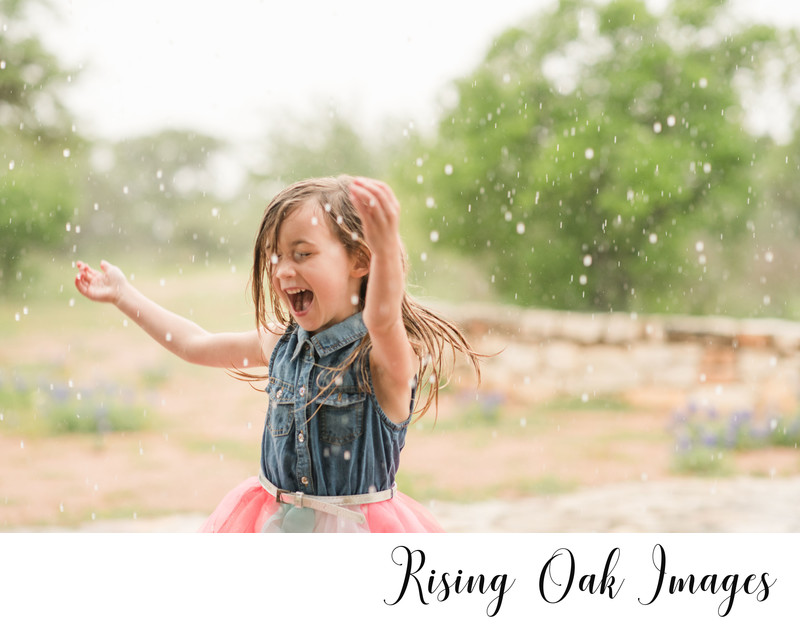 Little girl plays in rain in Dripping Springs photo