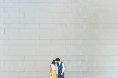 Engaged couple stands by wall at Butler Park in Austin
