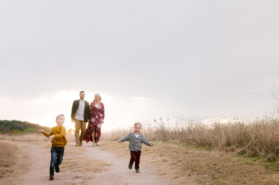 Kids run in front of parents in candid family fall photo in Austin