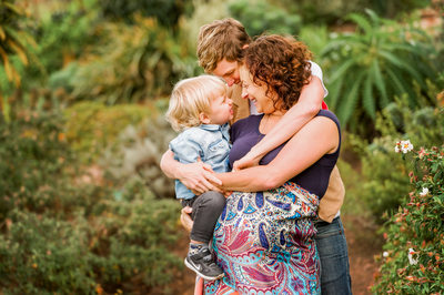 Two moms hug their little boy in Austin family photograph