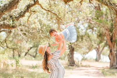 Candid maternity outdoor in Austin hill country with mom and daughter and baby bump